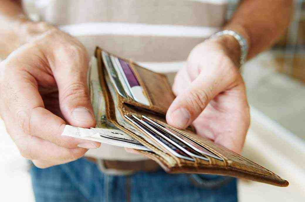 A close up of someone taking out bank notes from a wallet