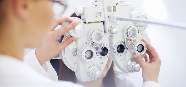 An Optician working with eye test equipment.