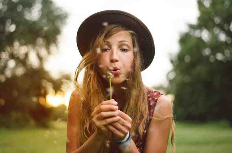 Image of a woman outside blowing on a dandilion